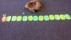 Kinderen gooien om de beurt met de 1, 2, 3 dobbelsteen en bij iedere worp verdwijnen er evenveel delen dan de rups in de mand als het aantal stippen dat is gegooid.