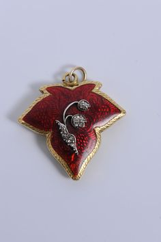 A Victorian yellow-metal, diamond-set and red-guilloche-enamel pendant locket in the form of an ivy leaf, with the lily-of-the-valley design set with rose-cut diamond chips; the ivy leaf symbolises the bonds of affection, while the lily of the valley denotes the return of happiness in the language of flowers.  (Reeman Dansie)