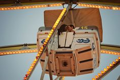 www.frostedproductions.com | #utah #photographer #engagement #photography #cute #photo #of #couple #kissing #on #a #ferris #wheel #lights #blue #sky
