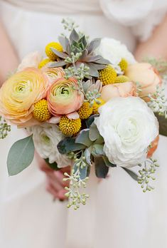 Brides.com: 15 Pretty Peach Bouquets. Mixed bouquet of ranunculuses, garden roses, craspedia, succulents, and seeded eucalyptus in shades of peach, yellow, and white by Studio Choo.