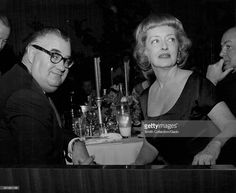 Bette Davis, sitting at a banquet table with an unidentified man, turning around in her chair and looking to her right, in a dark room during a dinner, Hollywood, California, Hollywood, California, 1950.