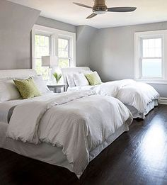 Soft gray wall color, with white bedding and pop of green.