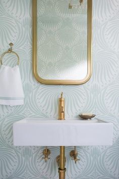 Sea foam green bathroom feature walls clad in green Farrow & Ball Lotus Wallpaper lined with a Restoration Hardware Astoria Flat Mirror placed above a white porcelain rectangular wall mount sink fitted with brushed brass faucet.