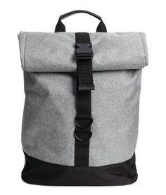 Graumeliert. Rucksack aus Webstoff mit Details aus Lederimitat. Rolltop-Modell mit Plastikschnalle zum Verstellen und Druckknopf auf beiden Seiten. Die