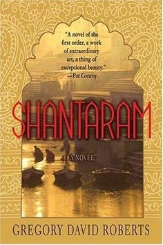 Shantaram: From a prison in the Pacific Ocean to Bombay India. A man escapes from prison, falsifies a passport, and flees to a poor slum of a city far away. With the help of his guide the two men navigate their way through a hidden society of gangsters, prostitutes, and exiles from other countries.