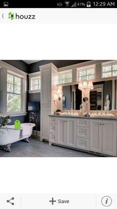 White cabinets, bathroom tub, dual sinks and mirrors