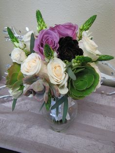 Lavender roses, purple lisianthus and ivory roses accented with green succulents and star of bethlehem