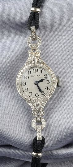 Lady's Art Deco Platinum and Diamond Wristwatch, the silver-tone metal dial with Arabic numeral indicators enclosing a replaced 17-jewel movement, the case bead-set with single-, and marquise-cut diamond melee, completed by black cord, dial signed Cartier, interior cir. 6 1/4 in.