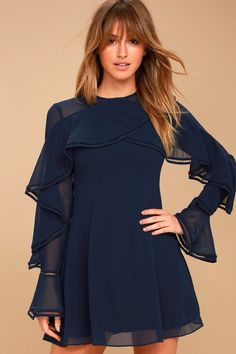 Twinkle among the city lights in the Keepsake Night Lights Navy Blue Long Sleeve Skater Dress! Lightweight Georgette cascades from a rounded neckline, into overlapping ruffles (with pierced crochet trim) that carry into sheer, long sleeves with flounce cuffs. Princess seams travel from a fitted bodice, into a flaring skater skirt. Hidden back zipper/clasp.