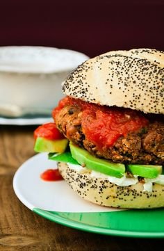 A close up of a juicy bean burger on a burger bun with avocado and salsa.