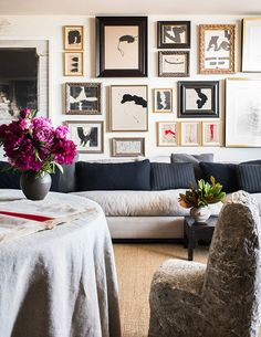 Modern gallery wall of mostly black and white artwork in a living room design - Gallery Wall Ideas & Decor