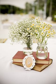 Beautiful wildflowers in jars as the main wedding centerpieces, and old books to add a bit of a vintage feel to the tables. Design by Moran Carmeli. Photo by Dan Miller.