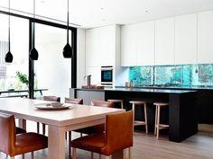 cuisine avec des armoires blanches, crédence aquarium, îlot central noir et coin repas