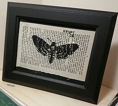 Framed book page painting of a death head moth onto a page from the Satanic Bible.  mrcrypt.bigcartel.com