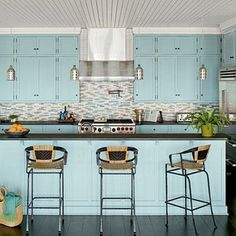 A light-blue shade on the cabinets and island complements the sea-inspired backsplash and softens stainless steel appliances and dark countertops and floors. coastalliving.com