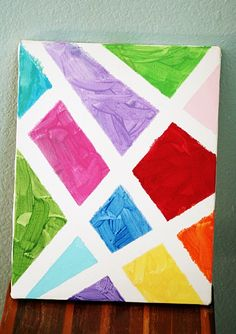 This looks fun for kids of all ages. Place masking tape in a design on a blank canvas (or heavy paper/poster board). For toddlers, why not use finger paint? What may look messy will become a work of art when the tape is removed!
