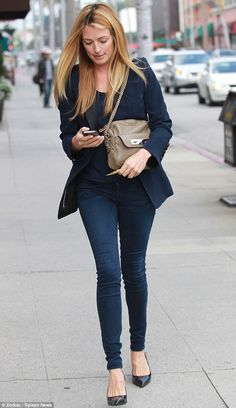 Shop 'til you drop: Cat looked effortlessly chic in a navy blue blazer jacket and vest, which she teamed with form-fitting skinny jeans and fierce spiked stilettos