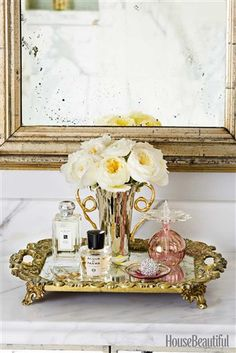Corral perfume bottles, jewelry and flowers on a small tray make a pretty, clutter-free countertop. (© John Granen)