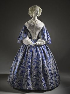 Womans Two-piece Dress France, circa 1855 Costumes; principal attire (entire body) Silk plain weave with supplementary weft-float patterning, silk satin, and silk-ribbon trim Center back bodice length: 14 1/4 in. (36.195 cm); Center back skirt length: 48 1/2 in. (123.19 cm)