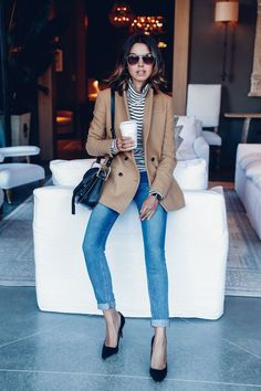 Striped turtleneck with cuffed jeans, black pumps, camel coat.
