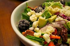 Blackberries, avocado, sliced red onions, cucumber, carrots, pecans and crumbled feta on a bed of red lettuce and spinach leaves.