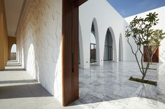 Arched openings in the sandstone facade of this Dubai mosque by Ibda Design lead worshippers into a bright marble courtyard with a textured minaret Minimalist Architecture, Contemporary Architecture, Architecture Design, Mosque Architecture, Religious Architecture, Indian Architecture, Dubai Design Week, Buddhist Shrine, Interior Garden