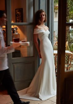 """This ivory crepe <a href=""""https://go.redirectingat.com?id=74679X1524629&sref=https%3A%2F%2Fwww.buzzfeed.com%2Fbetsydickerson%2Fpretty-wedding-dresses&url=http%3A%2F%2Fwww.bhldn.com%2Fshop-the-bride-wedding-dresses%2Fblake-gown%2Fproductoptionids%2Ffbcaeb8b-b90b-4e9a-9313-32da085940dd&xcust=4501909%7CBFLITE&xs=1"""" target=""""_blank"""">gown</a> with a criss-cross bodice, off-the-shoulder sleeves, and sweeping train."""