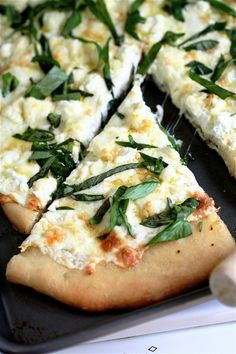 Four Cheese White Pizza  For the pizza:  3 TBLS olive oil, plus more for brushing the pan  3 tsp garlic, chopped (about 3 cloves)  8 oz (1/2 pound) fresh mozzarella, sliced and coarsely chopped  3 oz fresh goat cheese, crumbled  1/2 cup part-skim ricotta  1/4 cup Parmesan cheese, grated  3 TBLS thinly sliced fresh basil