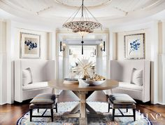 In the entry, a Venetia Studium fixture is set above a custom ashwood table and two natural linen side benches all on a custom wool-and-silk Orley Shabahang rug. A pair of cream-colored settées flank the entry hall, which leads to the main living space.