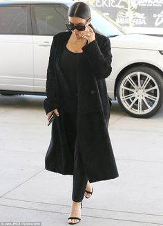 Keeping it simple: Kim wore a tank top and leggings under a thick coat, along with kitten ...