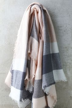 "Grab the Cheering Section Blush Pink Plaid Scarf, your hot cocoa, and get ready to cheer on your favorite team! Super soft woven fabric has a pink, grey, and white plaid print, plus fringe hems. Scarf measures 57"" wide, and 56"" long."