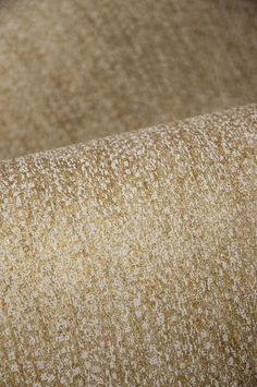Note Wallcovering - A shimmering textured wallpaper printed in beige and metallic gold with a distressed effect.