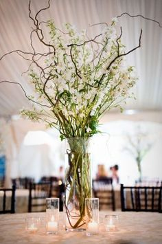 White and green flowers with tall branch centerpiece