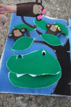 """I loved making the farm finger puppets so much that I went ahead and made monkeys for the """"5 little monkeys teasing Mr. Alligator"""". Mr. Alligator is a pocket that can 'eat' the monkeys and each monkey has a leaf in the tree to sit in to tease from. I made this page up myself …"""