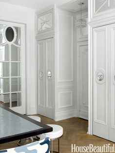 """To give presence to a standard entry door and separate it from the kitchen, designer Kelly Giesen created a """"foyer"""" by framing the door with closets and a transom all dressed up with mirrors and molding."""