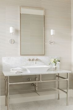 Elegant bathroom features walls clad in gray grasscloth wallpaper lined with an extra-wide polished nickel and marble washstand topped with a white vessel sink under a faucet mounted on a marble backsplash situated under rivet vanity mirror illuminated by Hudson Valley Lighting Aberdeen Sconces.