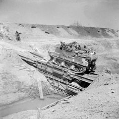 A Sexton 25pdr self-propelled gun crossing the River Senio over two Churchill Ark bridging tanks, 10 April 1945.