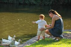 2 year old Charley and Mom feeding ducks at Lakeside Park in Highland Park, Texas