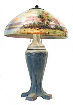 HANDEL REVERSE-PAINTED GLASS AND PATINATED METAL TABLE LAMP  20th Century. Signed JBailey, Handel, and numbered 737.  Shade Diameter 17 1/2,  Height 26 inches.