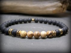 A mens earthy and natural stone beaded stretch bracelet with picture jasper stones and black matte stones accented with solid brass double ring beads.