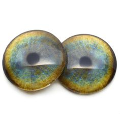 These handmade glass eye cabochons depict realistically rendered, tan and light blue leopard glass eyes. These leopard glass eyes contain small round, black pupils surrounded with a textured and realistically shaded iris. These glass eyes are perfect for jewelry making, art dolls, bottle cap pendants, taxidermy projects, scrap booking, paper mâché sculptures, or other crafting projects. This glass eye design is available in sizes 40mm, 30mm, 25mm, and 20mm, 16mm, 14mm, 12mm, 10mm, 8mm, and 6mm.