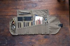 Waxed Canvas Sendak Artist Roll Up Case holds pens, pencils, tools, brushes, and notebooks in pockets and zipper pouch. Leather closure.