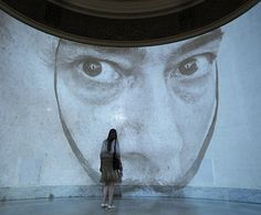 Moscow, Russia: A visitor looks at a projection of a picture of Salvador Dali during an exhibition of his work at the Pushkin Museum