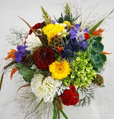 textures and colors and a funky assortment of flowers makes this bouquet extra special. Red dahlias, orange coxcomb, brown scabiosa pods, yellow calendula, explosion grass, succulents.... a great summer bridal bouquet. Flowers by April's Garden in Durango,CO http://www.durangoflorist.com/