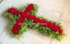 Cross tribute of luxurious red roses on a bed of seasonal yellow flowers