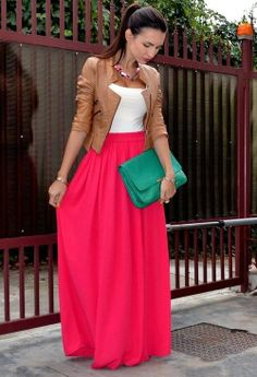 Jaqueta marrom. Saia longa pink e carteira verde.