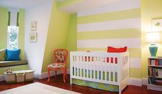 Shelter Interior Design Adorable gender neutral nursery design with yellow & white striped walls paint color, white modern crib, blue & green crib bedding, built-in window seat, blue & yellow pillows, blue lamp, orange chair and orange pillow.