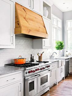 A contemporary backsplash tile in a neutral color complements the countertops and cabinets. Countertops in warm, dark grays keep the monochromatic scheme from feeling cold. The wood-wrapped range hood adds warmth and natural beauty to the room.