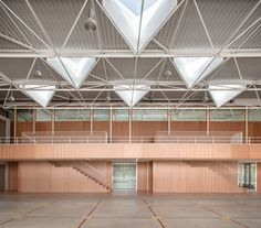 Sports hall for Escola Gavina school in Spain features multi-hued clay and glass tiles