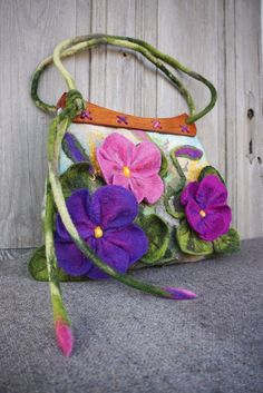 Hand felted bag, large shoulder bag with beautiful 3D purple spring flowers. Handcrafted wooden handles add to it unique character. These handles were made from exotic wood by my husband for basis of a vintage model which I used to my previous bags. Most beautiful and spectacular than on a picture! Flowers is not sewn but felted together with a bag! I made it using nuno felted technique with fine merino wool on vintage hand painted silk scarf. Bag strap is strengthened inside with cotton…